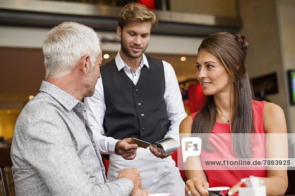 Paar,  das mit einer Kreditkarte an einen Kellner in einem Restaurant zahlt.