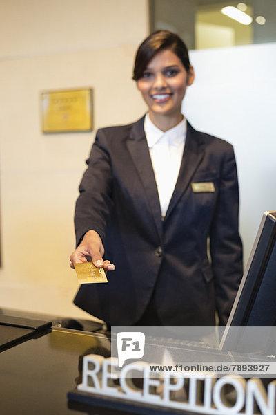 Rezeptionistin mit Kreditkarte und Lächeln an der Hotelrezeption