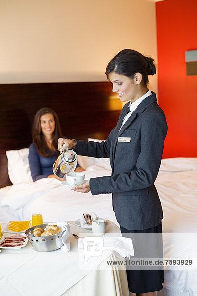 Kellnerin  die einer Frau im Hotelzimmer Tee serviert.