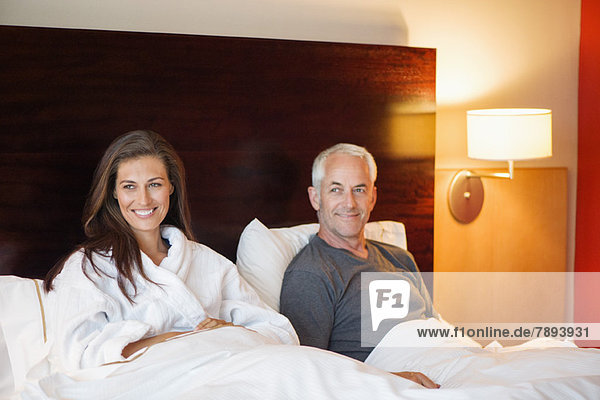 Paar im Hotelzimmer auf dem Bett sitzend