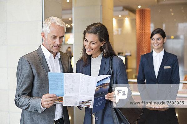 Geschäftsleute beim Lesen einer Broschüre vor einer Hotelrezeption