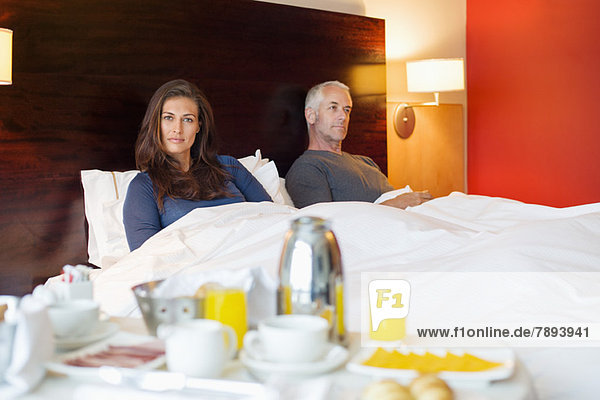 Breakfast on table in front of a couple in a hotel room