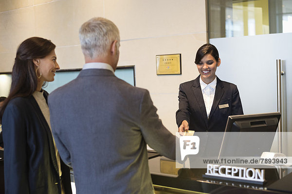 Geschäftsleute  die mit einer Kreditkarte an der Rezeption des Hotels bezahlen