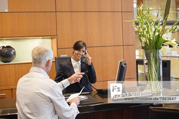 Rezeptionist im Gespräch mit einem Geschäftsmann  der auf die Rezeption des Hotels zeigt.