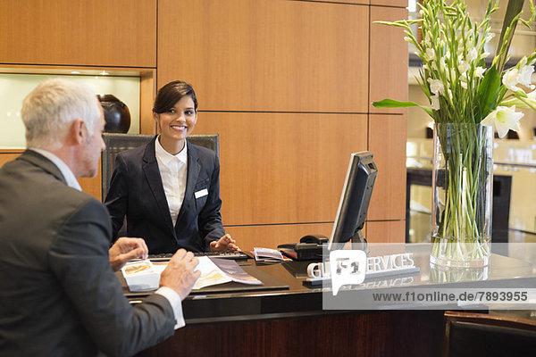 Geschäftsmann im Gespräch mit einer Rezeptionistin an der Hotelrezeption