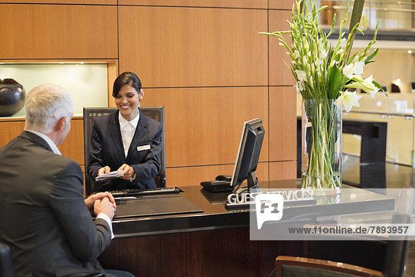 Rezeptionistin  die einem Geschäftsmann an der Hotelrezeption Broschüren überreicht.