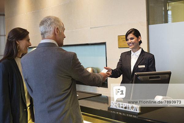 Geschäftsleute erhalten Schlüsselkarte an der Hotelrezeption