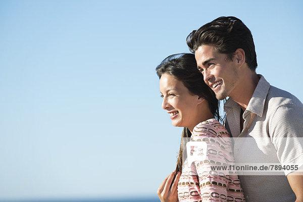 Romantisches Paar lächelt am Strand