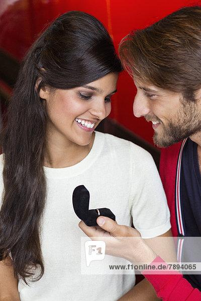 Ein Mann  der seiner Freundin in einem Restaurant einen Antrag macht.