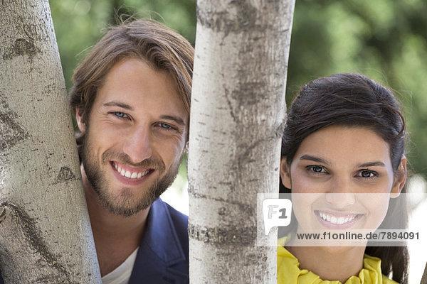 Porträt eines Paares  das hinter einem Baum lächelt