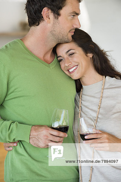 Paar hält Weingläser und lächelt