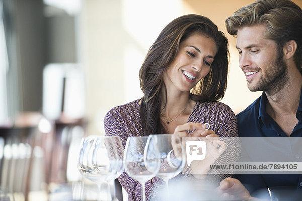 Mann  der seiner Freundin in einem Restaurant einen Verlobungsring schenkt.