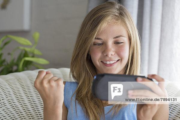 Nahaufnahme eines lächelnden Mädchens beim Videospiel