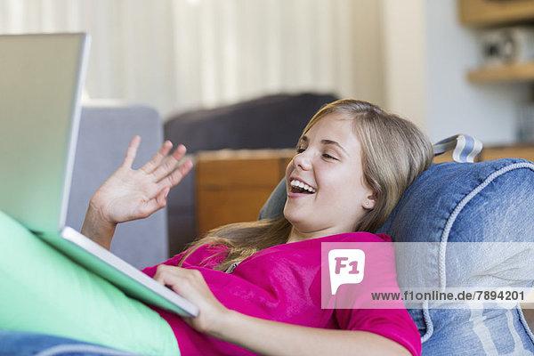 Girl Video-Chat auf einem Laptop und lächeln