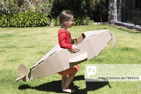 Mädchen beim Spielen mit einem Flugzeug aus Pappe im Rasen