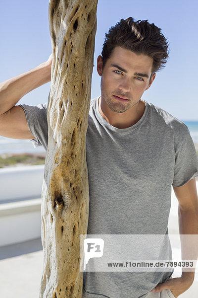 Mann steht neben einem Holzpfosten