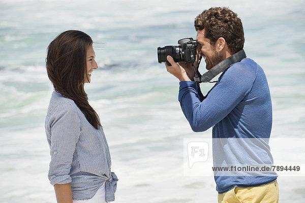 Mann beim Fotografieren seiner Frau mit einer Kamera am Strand