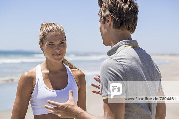 Frau im Gespräch mit ihrem Trainer am Strand