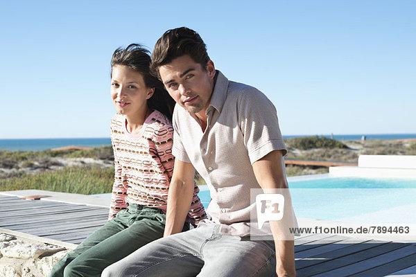 Paar auf einer Strandpromenade am Strand sitzend