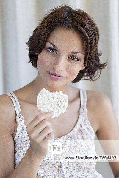 Porträt einer Frau beim Essen von Reiskuchen