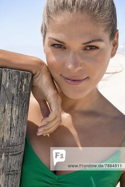 Frau  die sich an einen Holzpfosten am Strand lehnt.