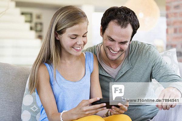 Vater und Tochter spielen ein Videospiel und lächeln zu Hause