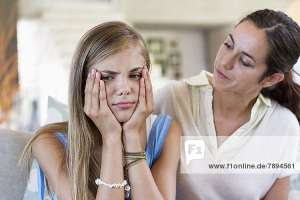 Frau  die ihre verärgerte Tochter zu Hause überredet.