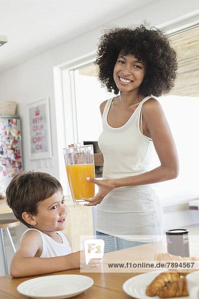 Frau und Sohn am Esstisch mit Orangensaft