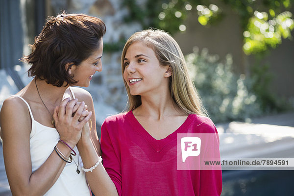 Nahaufnahme einer Frau und ihrer Tochter beim gemeinsamen Lächeln