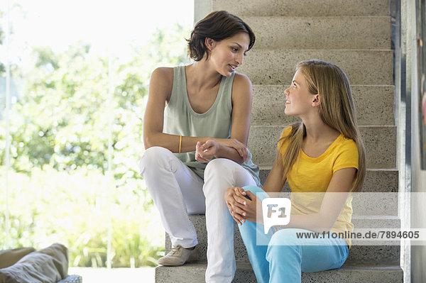 Mutter und Tochter sitzen auf einer Treppe und reden miteinander.