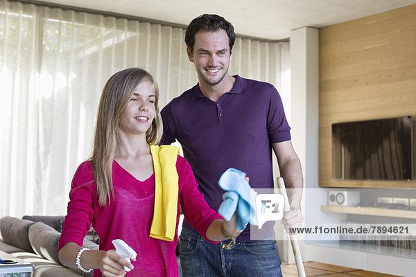 Mädchen beim Putzen einer Glastür neben ihrem Vater
