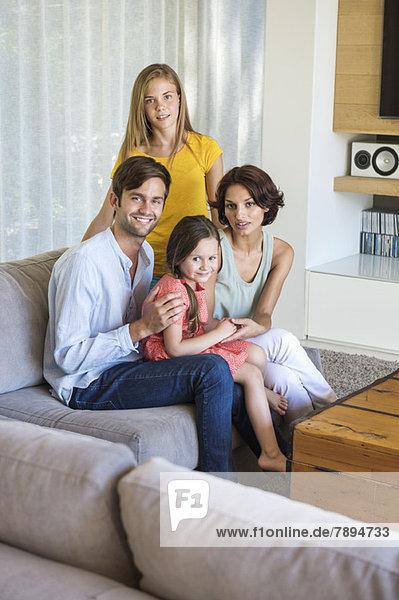 Eltern mit ihren Kindern sitzen im Wohnzimmer
