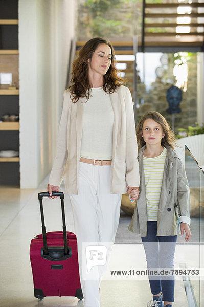 Frau  die mit ihrer Tochter mit Gepäck geht