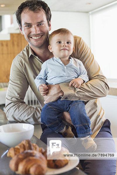 Mann mit seinem Sohn lächelnd an der Küchentheke