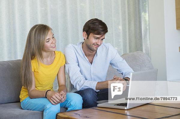 Mann und seine Tochter sitzen auf einer Couch und schauen auf einen Laptop.