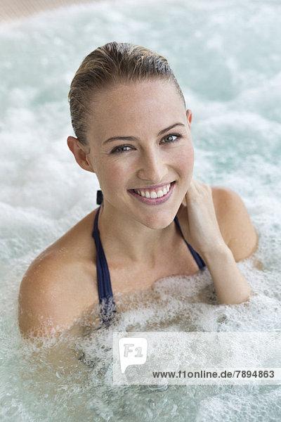 Porträt einer lächelnden schönen Frau im Whirlpool