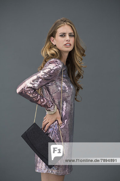 Porträt einer Frau  die mit einer Handtasche posiert