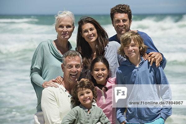 Porträt einer am Strand lächelnden Familie