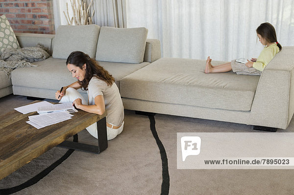 Woman doing paperwork with her daughter using a digital tablet at home
