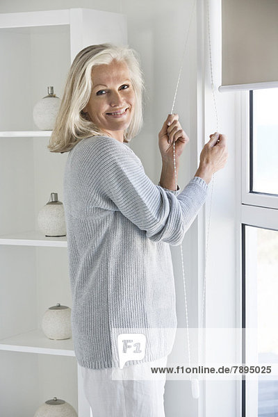 Woman adjusting window curtain
