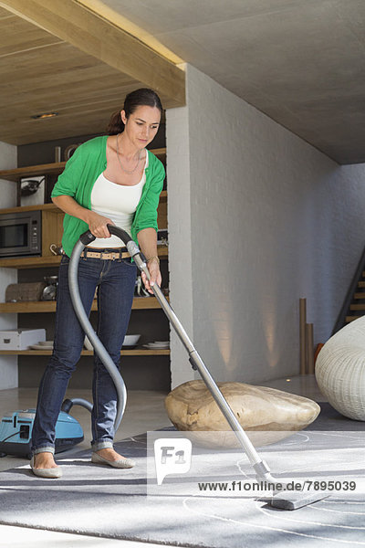 Woman cleaning house with a vacuum cleaner
