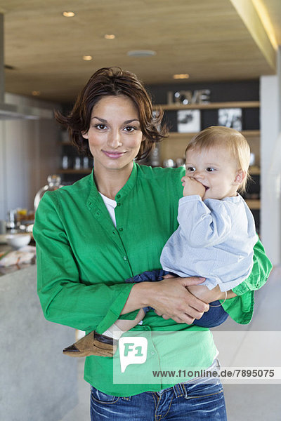 Woman carrying her son and smiling at home