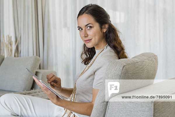 Beautiful woman using a digital tablet on a couch