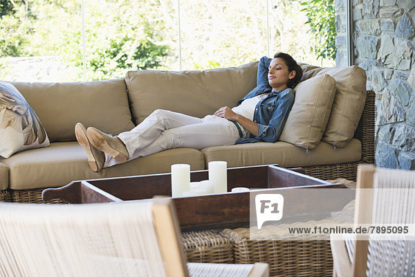 Woman lying on a couch in a living room