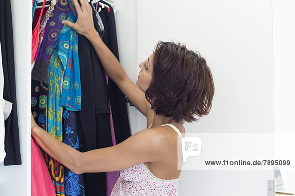Woman choosing clothes from wardrobe