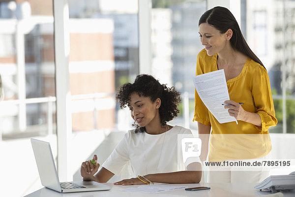 Zwei Freundinnen beim Durchsehen der Rechnung auf einem Laptop zu Hause