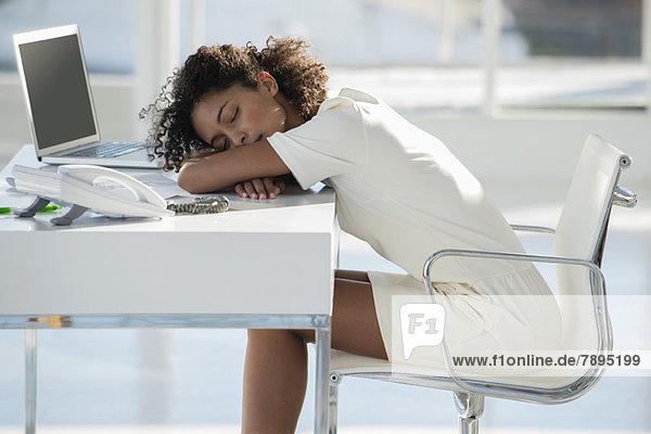 Frau schlafend mit dem Kopf auf dem Schreibtisch liegend