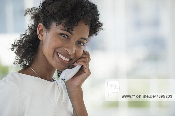 Porträt einer Frau am Festnetztelefon