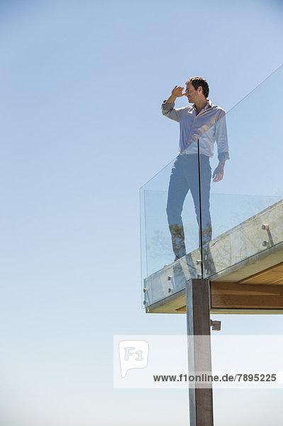 Mann steht auf der Terrasse und schirmt seine Augen ab.