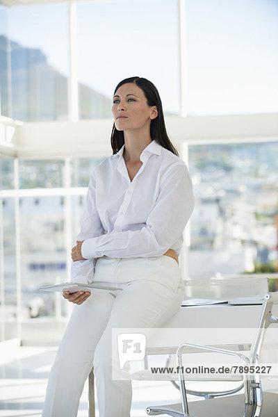 Geschäftsfrau denkt mit dem Halten eines digitalen Tabletts in einem Büro